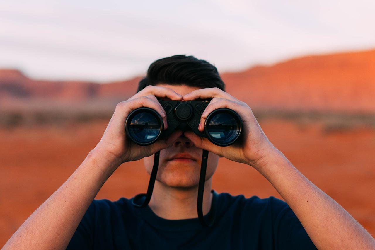 uomo con binocolo nel deserto